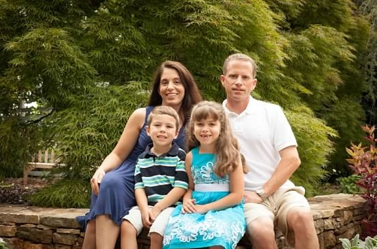 Family picture of happy parents and little kids on the garden at a Preschool & Daycare/Childcare Center serving Apex & Fuquay-Varina, NC