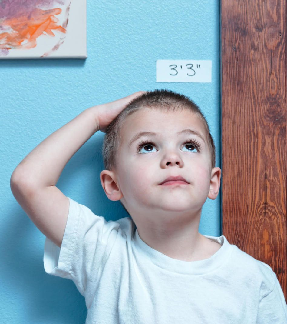 Young kid boy measuring his height at a Preschool & Daycare/Childcare Center serving Apex & Fuquay-Varina, NC