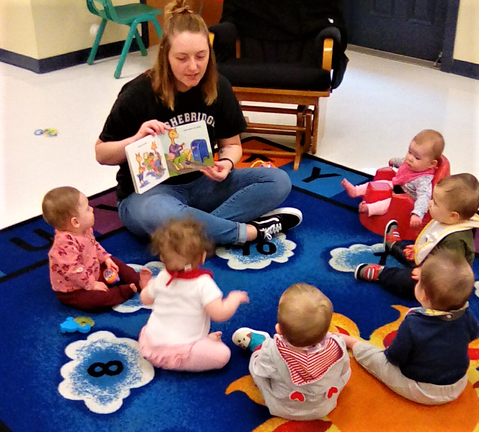 Teacher reading a story with group of cute little babies at a Preschool & Daycare/Childcare Center serving Apex & Fuquay-Varina, NC