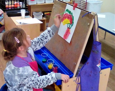 Preschool kid girl showing artistry doing paintings at a Preschool & Daycare/Childcare Center serving Apex & Fuquay-Varina, NC