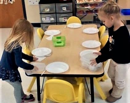 Young little preschool girls on discovering roles, preparing plates on the table at a Preschool & Daycare/Childcare Center serving Apex & Fuquay-Varina, NC