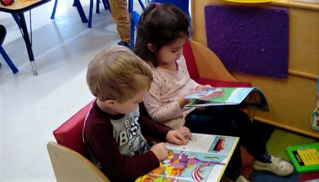 Two toddlers reading educational book for early literacy at a Preschool & Daycare/Childcare Center serving Apex & Fuquay-Varina, NC