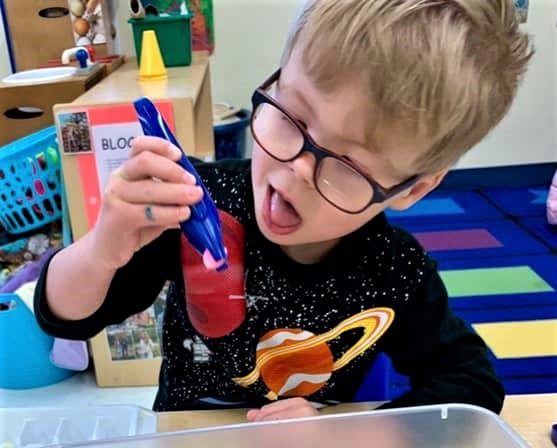 Kid boy showing curiosity playing with educational toys at a Preschool & Daycare/Childcare Center serving Apex & Fuquay-Varina, NC