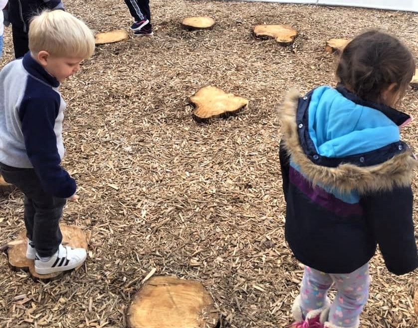 home naturalizing playgrounds, toddlers playing on cut truck of trees at a Preschool & Daycare/Childcare Center serving Apex & Fuquay-Varina, NC
