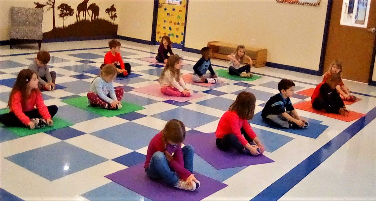 Preschoolers on positive behavior management, doing yoga inside the class at a Preschool & Daycare/Childcare Center serving Apex & Fuquay-Varina, NC