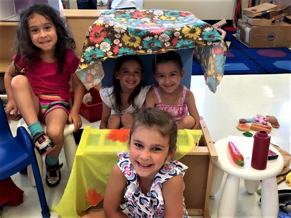 Group of smiling young little girls showing creativity at a Preschool & Daycare/Childcare Center serving Apex & Fuquay-Varina, NC