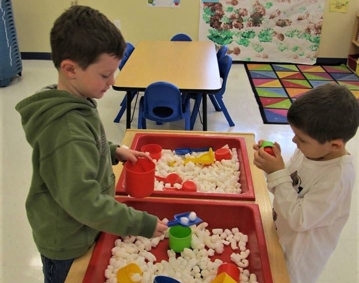 Two young kid boys playing with educational toys at a Preschool & Daycare/Childcare Center serving Apex & Fuquay-Varina, NC
