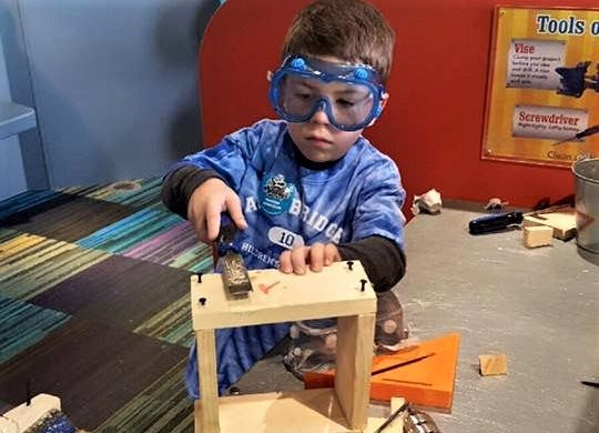 Young little kid boy wearing protective glasses doing carpentry playing with plastic safe tools at a Preschool & Daycare/Childcare Center serving Apex & Fuquay-Varina, NC