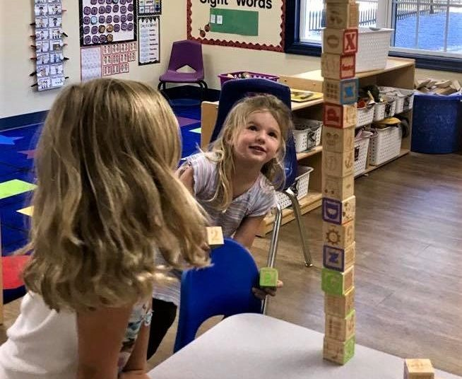Young little preschool girls looking stacked wooden lettered cubes at a Preschool & Daycare/Childcare Center serving Apex & Fuquay-Varina, NC