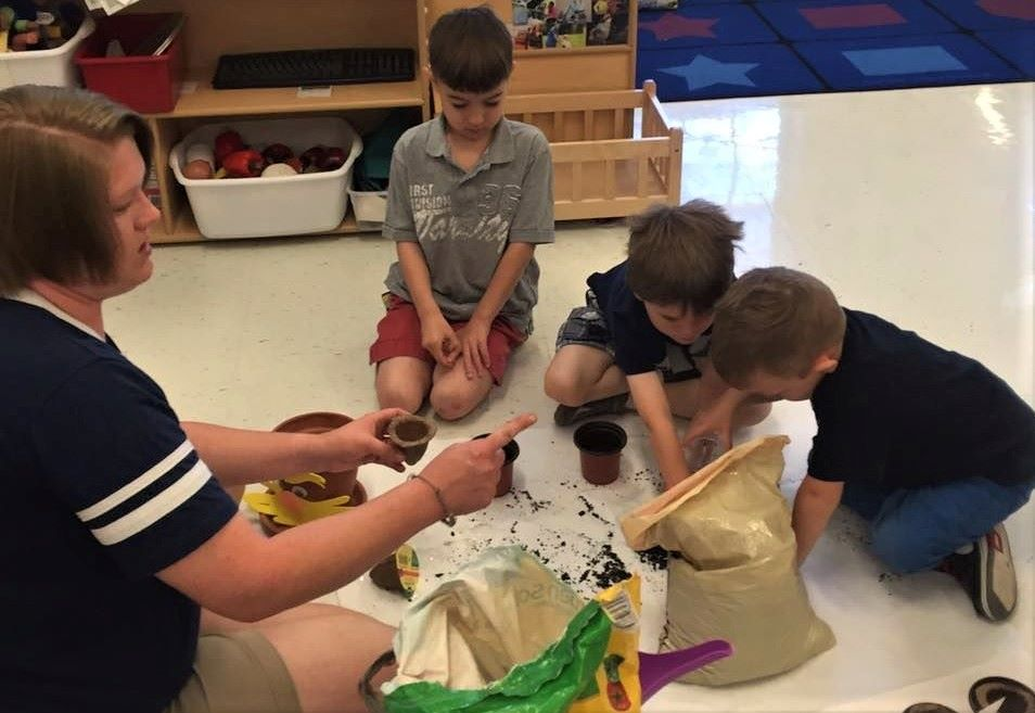 Preschool boys getting some soil inside a sack and putting them on a small pot for gardening activity at a Preschool & Daycare/Childcare Center serving Apex & Fuquay-Varina, NC