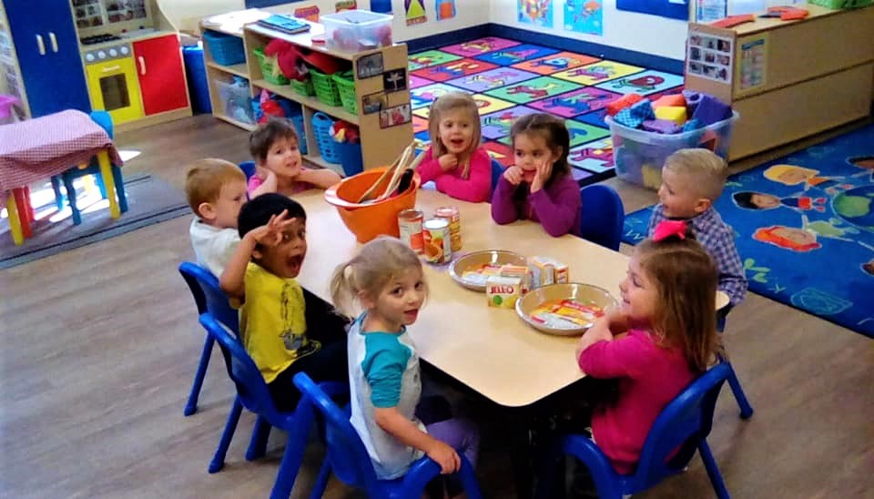 preschool children showing social interactions, gather around a table preparing for the day activity at a Preschool & Daycare/Childcare Center serving Apex & Fuquay-Varina, NC