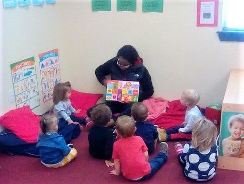Teacher showing colorful pages of story book to group of toddlers