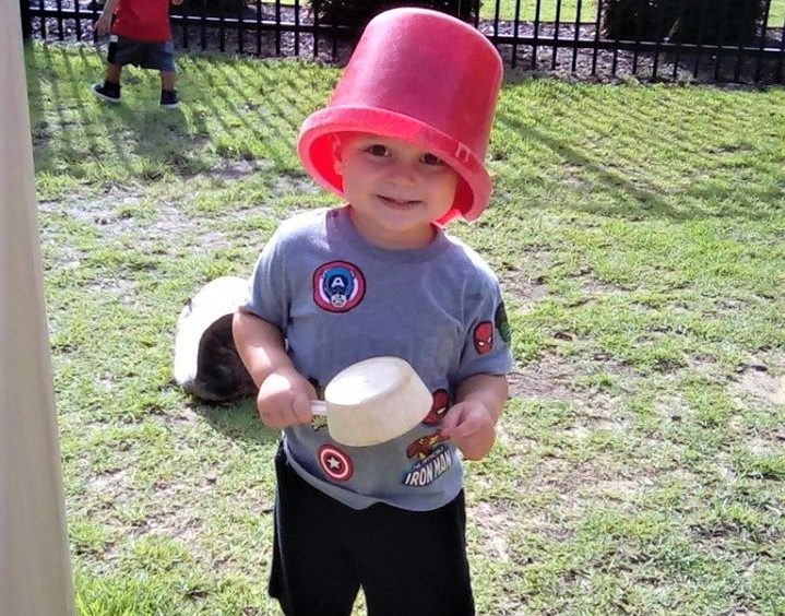 Happy toddler boy playing in the school yard with a red bucket in his head and holding a plastic scooper at a Preschool & Daycare/Childcare Center serving Apex & Fuquay-Varina, NC