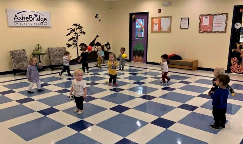 Toddlers on a large room playing at a Preschool & Daycare/Childcare Center serving Apex & Fuquay-Varina, NC