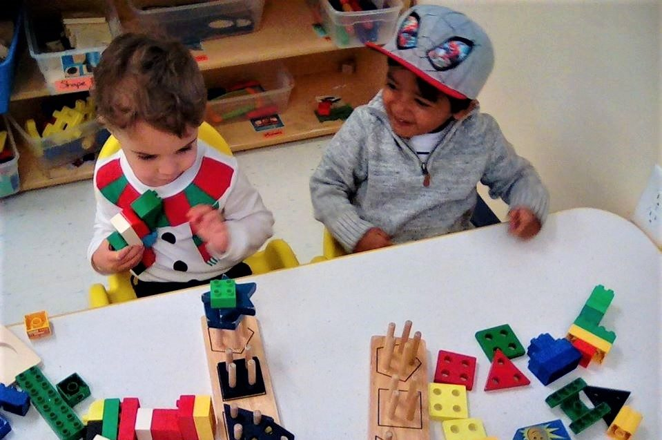 Toddlers showing math skills, playing with developmental building blocks at a Preschool & Daycare/Childcare Center serving Apex & Fuquay-Varina, NC