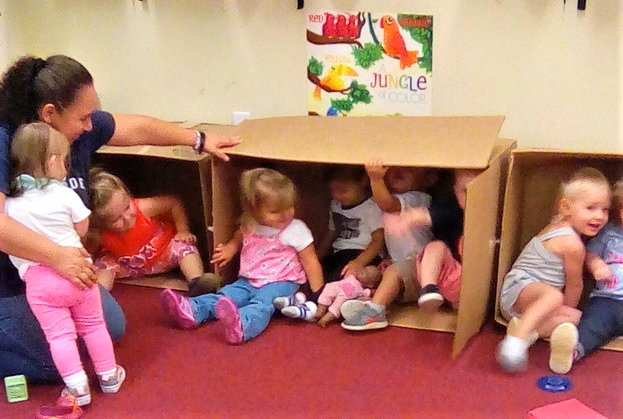 Toddlers playing inside big boxes at a Preschool & Daycare/Childcare Center serving Apex & Fuquay-Varina, NC