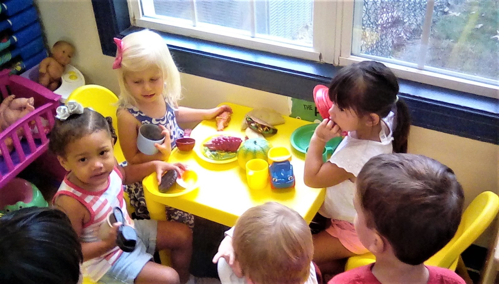 Preschool children playing with plastic educational kitchen food , being part of family at a Preschool & Daycare/Childcare Center serving Apex & Fuquay-Varina, NC