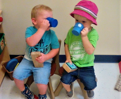 Two toddler boys drinking on cups while sitting at a Preschool & Daycare/Childcare Center serving Apex & Fuquay-Varina, NC
