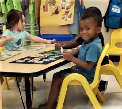 African american preschool boy with other preschoolers working with art activity at a Preschool & Daycare/Childcare Center serving Apex & Fuquay-Varina, NC
