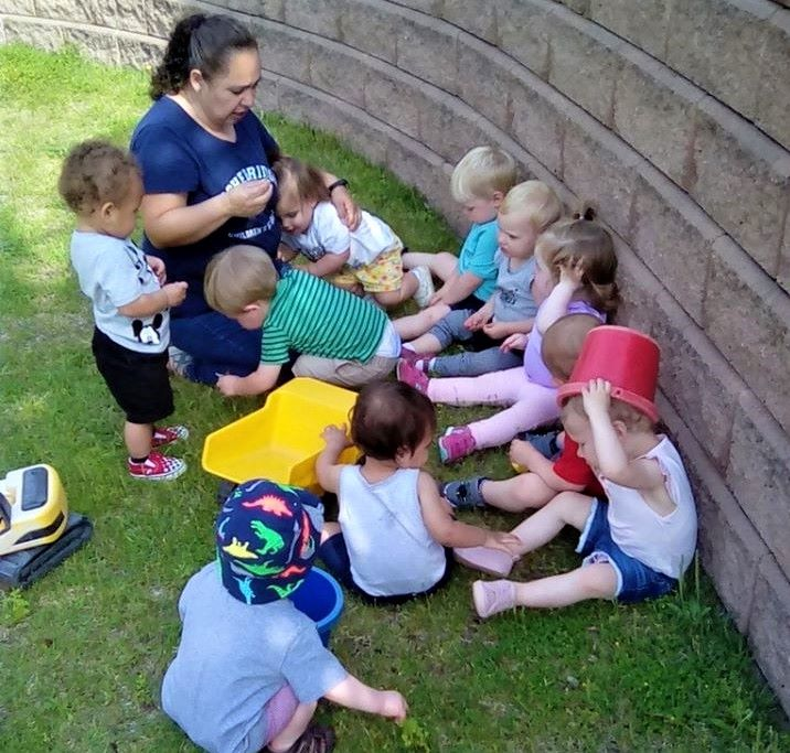 Teachers with toddlers gather around teaching and demonstrating daily kindness at a Preschool & Daycare/Childcare Center serving Apex & Fuquay-Varina, NC