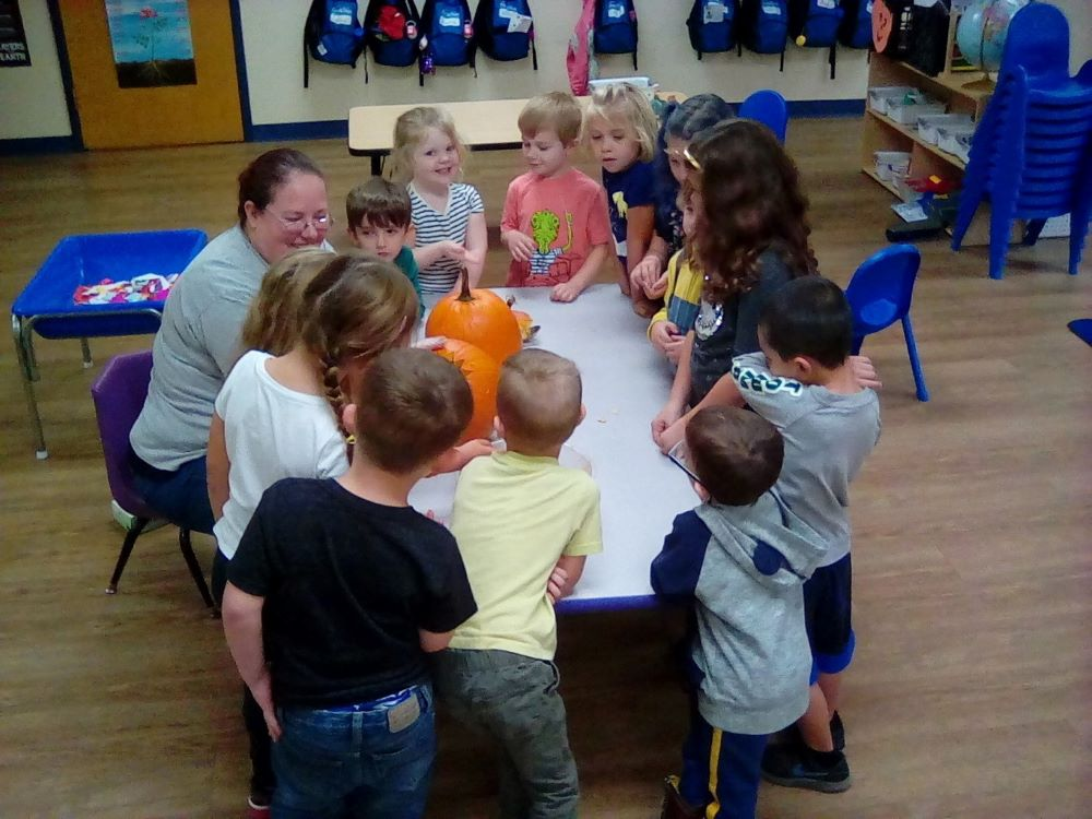 Teacher with young little preschool kids gather around with pumpkins in the table at a Preschool & Daycare/Childcare Center serving Apex & Fuquay-Varina, NC