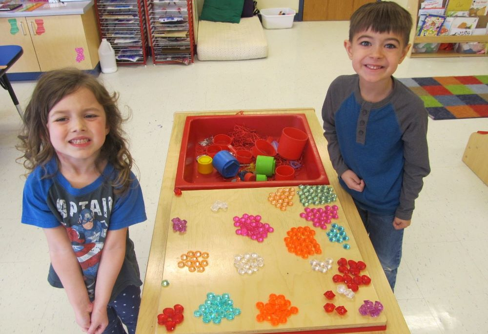 Preschool kids boy and girl playing with colorful educational gem like beads at a Preschool & Daycare/Childcare Center serving Apex & Fuquay-Varina, NC