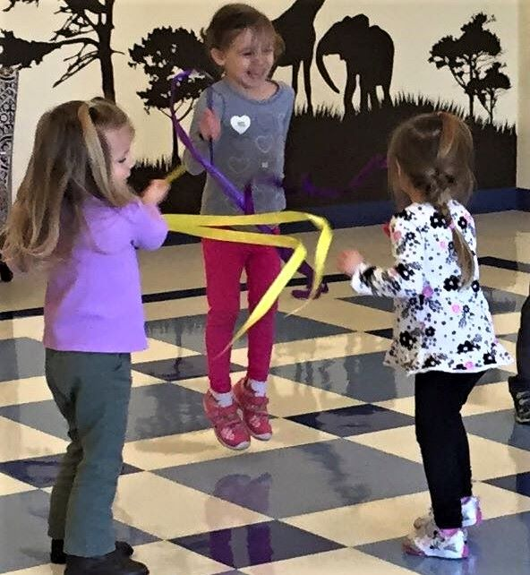 Young little girls jumping, enjoying, and playing with music at a Preschool & Daycare/Childcare Center serving Apex & Fuquay-Varina, NC